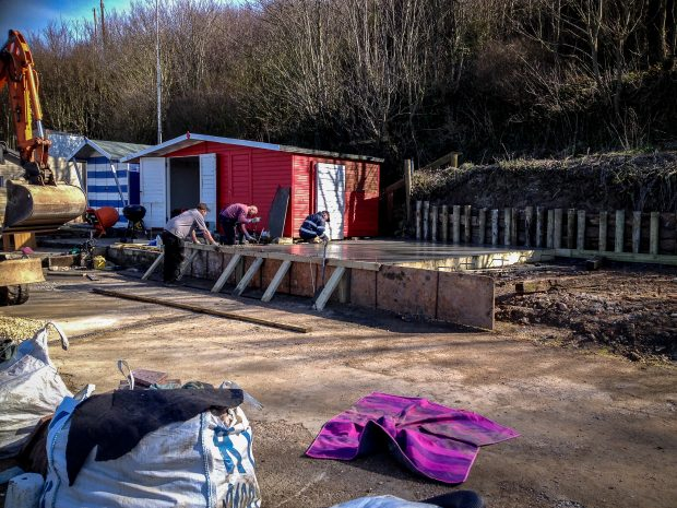 Photo showing workman building decking for new Beach Huts at Colwell Bay, Isle of Wight. March 2014.